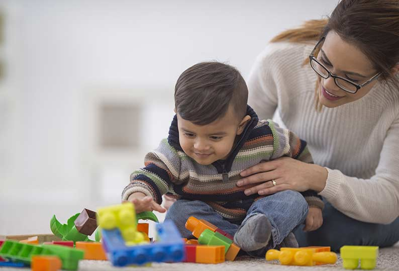 Baby boy reaching for rainbow blocks with mother holding him
